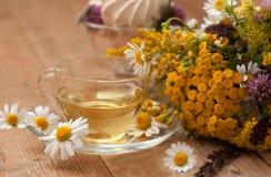 Eine Schale des Kamillenteen in einer Glasschale, der Schüssel Eibische und des Blumenstraußes des Feldsommers blüht auf einer Ho Lizenzfreie Stockfotos
