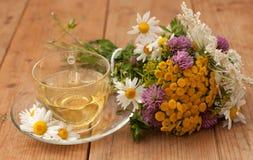 Eine Schale des Kamillenteen in einer Glasschale und des Blumenstraußes des Feldsommers blüht auf einer Holzoberfläche Stockfotografie