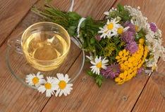 Eine Schale des Kamillenteen in einer Glasschale und des Blumenstraußes des Feldsommers blüht auf einer Holzoberfläche Lizenzfreie Stockfotografie
