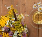 Eine Schale des Kamillenteen in einer Glasschale und des Blumenstraußes des Feldsommers blüht auf einer Holzoberfläche Lizenzfreies Stockbild