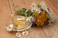 Eine Schale des Kamillenteen in einer Glasschale und des Blumenstraußes des Feldsommers blüht auf einer Holzoberfläche Stockfoto