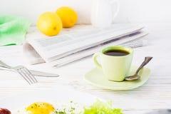 Eine Schale des schwarzen Kaffees, der Zeitung und des Tischbestecks auf einer weißen Tabelle stockfoto