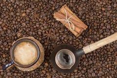 Eine Schale frisch gebrauter Kaffee, Topf und Zimt auf Kaffeebohnen Stockfotos