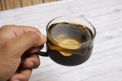 Eine Schale grüner Tee mit choco Chips cookiesMen ` s Hand, die eine Schale grünen Tee hält, um zu trinken Lizenzfreie Stockfotos