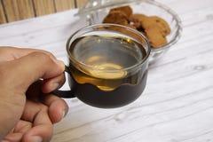 Eine Schale grüner Tee mit choco Chips cookiesMen ` s Hand, die eine Schale grünen Tee hält, um zu trinken stockbilder