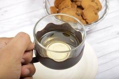 Eine Schale grüner Tee mit choco Chips cookiesMen ` s Hand, die eine Schale grünen Tee hält, um zu trinken stockbild