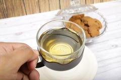 Eine Schale grüner Tee mit choco Chips cookiesMen ` s Hand, die eine Schale grünen Tee hält, um zu trinken Lizenzfreie Stockfotografie