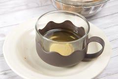 Eine Schale grüner Tee mit choco schneidet Plätzchen in Stücke stockfotografie