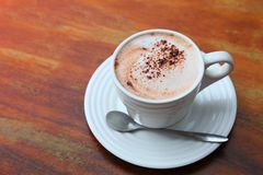 Eine Schale heiße Schokolade mit Kakaopulver diente auf Holztisch lizenzfreie stockfotos