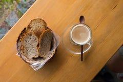 Eine Schale heißer Cappuccino und Brot Stockfotografie