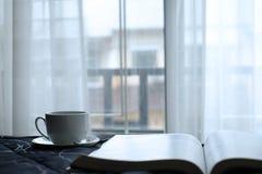 Eine Schale heißer Kaffee im Bett mit schöner Aussicht und weißem Vorhang vom Fenster stockfoto