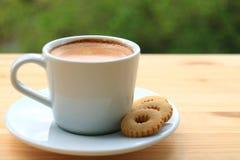 Eine Schale heißer Kaffee mit den Plätzchen gedient auf Holztisch Lizenzfreie Stockfotos