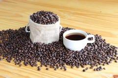 Eine Schale heißer Kaffee mit Röstkaffeebohnen auf dem Holztisch Stockbilder