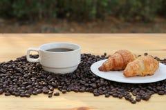 Eine Schale heißer Kaffee und auf gebratenem Bohnenhörnchen mit bokeh Hintergrund Lizenzfreies Stockbild