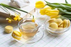 Eine Schale heißer Tee, gelbe Tulpen, gelbe Narzissen, alte Bücher und Zitronenmakronen auf einem hellen Hintergrund Stockfotografie