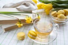 Eine Schale heißer Tee, gelbe Tulpen, gelbe Narzissen, alte Bücher und Zitronenmakronen auf einem hellen Hintergrund Stockbild