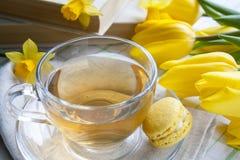 Eine Schale heißer Tee, gelbe Tulpen, gelbe Narzissen, alte Bücher und Zitronenmakronen auf einem hellen Hintergrund Lizenzfreie Stockbilder