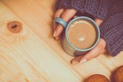 Eine Schale Kakao in den Händen auf einem hölzernen Hintergrund Blaue Strickjacke Lizenzfreie Stockfotografie