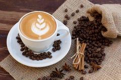 Eine Schale Lattekaffee und Kaffeebohnen lizenzfreie stockbilder