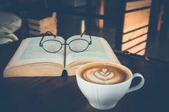 Eine Schale Lattekunst mit Augengläsern auf offenem Buch im Café Lizenzfreie Stockbilder