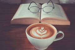 Eine Schale Lattekunst mit Augengläsern auf offenem Buch im Café Stockfoto