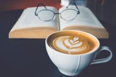 Eine Schale Lattekunst mit Augengläsern auf offenem Buch im Café Stockfotografie