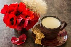 Eine Schale Milch nahe bei einem Blumenstrauß von Mohnblumen und von Löwenzahn Lizenzfreie Stockbilder