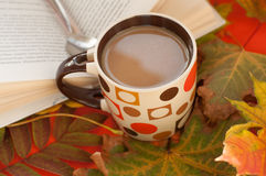 Eine Schale Milchkaffee, Löffel, geöffnetes Buch und bunter Herbstlaub Lizenzfreie Stockbilder