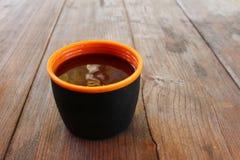 Eine Schale mit einem Getränk auf einem Holztisch draußen Stockfotos