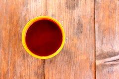 Eine Schale mit einem Getränk auf einem Holztisch draußen Stockbilder