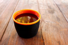 Eine Schale mit einem Getränk auf einem Holztisch draußen Lizenzfreies Stockbild