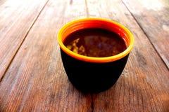 Eine Schale mit einem Getränk auf einem Holztisch draußen Stockfotografie