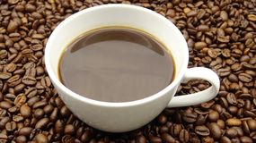 Eine Schale schwarzer Kaffee über Röstkaffeebohnen stockfotografie