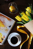 Eine Schale schwarzer Kaffee und ein Blumenstrauß von gelben Tulpen im Kraftpapier auf dem Tisch Buch mit hellen Bildern Stockfoto