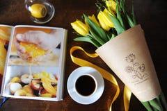 Eine Schale schwarzer Kaffee und ein Blumenstrauß von gelben Tulpen im Kraftpapier auf dem Tisch Buch mit hellen Bildern Lizenzfreie Stockbilder