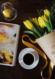 Eine Schale schwarzer Kaffee und ein Blumenstrauß von gelben Tulpen im Kraftpapier auf dem Tisch Buch mit hellen Bildern Stockfotos