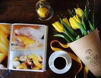 Eine Schale schwarzer Kaffee und ein Blumenstrauß von gelben Tulpen im Kraftpapier auf dem Tisch Buch mit hellen Bildern Stockbild