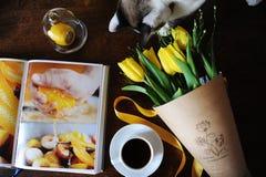 Eine Schale schwarzer Kaffee und ein Blumenstrauß von gelben Tulpen im Kraftpapier auf dem Tisch Buch mit hellen Bildern Nette Ka Stockfotos