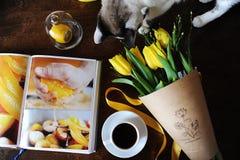 Eine Schale schwarzer Kaffee und ein Blumenstrauß von gelben Tulpen im Kraftpapier auf dem Tisch Buch mit hellen Bildern Nette Ka Stockbilder