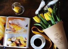 Eine Schale schwarzer Kaffee und ein Blumenstrauß von gelben Tulpen im Kraftpapier auf dem Tisch Buch mit hellen Bildern Nette Ka Lizenzfreies Stockfoto