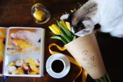 Eine Schale schwarzer Kaffee und ein Blumenstrauß von gelben Tulpen im Kraftpapier auf dem Tisch Buch mit hellen Bildern Nette Ka Lizenzfreie Stockbilder