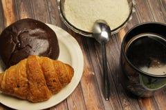Eine Schale schwarzer Kaffee und Gebäck lizenzfreie stockbilder