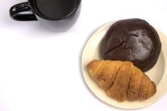 Eine Schale schwarzer Kaffee und Gebäck lizenzfreies stockbild