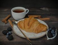Eine Schale schwarzer Tee mit einem frischen goldenen Hörnchen und Beeren Auf einem hölzernen Hintergrund Frische Bäckerei stockfotografie