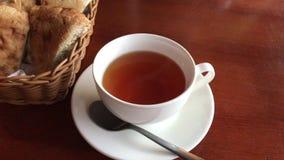 Eine Schale Stände des schwarzen Tees auf einer braunen Tabelle, nahe bei einem Korb des geschnittenen Brotes stock footage