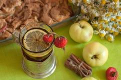 Eine Schale starker schwarzer Tee mit einer Zitronenscheibe, einem Apfelkuchen, einem Blumenstrauß der Kamille, Zimtstangen, reif Stockfotografie