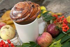 Eine Schale starker schwarzer Tee, süßes Brötchen mit Rosinen, Aschbeeren, Äpfel und bunter Herbstlaub auf einer Steinoberfläche Lizenzfreie Stockfotos