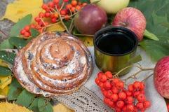 Eine Schale starker schwarzer Tee, süßes Brötchen mit Rosinen, Aschbeeren, Äpfel und bunter Herbstlaub auf einer Steinoberfläche Stockfoto