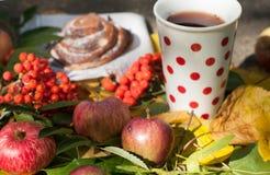 Eine Schale starker schwarzer Tee, süßes Brötchen mit Rosinen, Aschbeeren, Äpfel und bunter Herbstlaub auf einer Steinoberfläche Lizenzfreie Stockfotografie