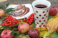 Eine Schale starker schwarzer Tee, süßes Brötchen mit Rosinen, Aschbeeren, Äpfel und bunter Herbstlaub auf einer Steinoberfläche Stockfotografie